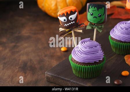Festliche Halloween Cupcakes mit bunten Dekorationen. Marshmallow in Schokolade mit gruseligen Monstern. Platz kopieren, selektiven Fokus. - Stockfoto