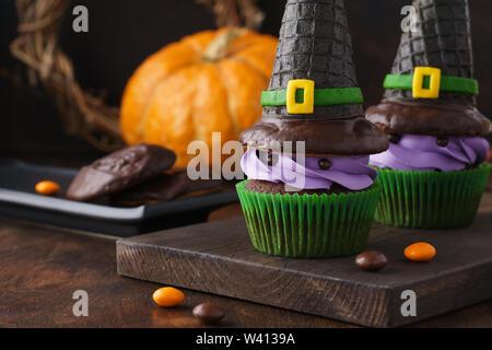 Festliche Halloween Cupcakes mit wafer Hexe Hüte, Süßigkeiten und Schokolade Cookies. - Stockfoto