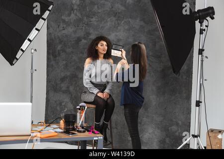 Portrait von weiblichen make-up-artist Anwendung Kosmetik Pretty Woman während Foto Shooting mit professionellen Kamera und softbox im Studio - Stockfoto