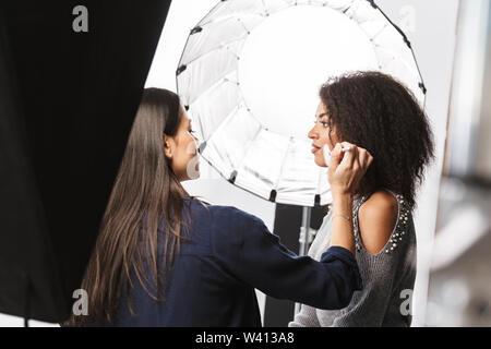 Portrait von weiblichen make-up-artist Anwendung Kosmetik zu wunderschönen Frau beim Foto Shooting mit professionellen Kamera und softbox im Studio - Stockfoto