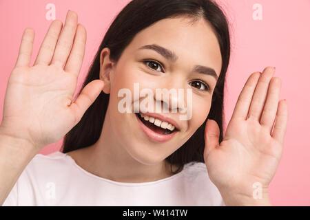 Portrait Nahaufnahme des charmanten kaukasische Mädchen mit langen dunklen Haaren, Augen und spähen obwohl Finger über rosa Hintergrund isoliert - Stockfoto