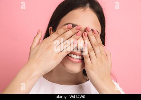 Portrait Nahaufnahme von süßen fröhliches Mädchen mit langen dunklen Haaren, Augen und spähen obwohl Hände über rosa Hintergrund isoliert - Stockfoto