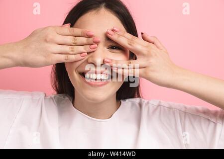 Portrait Nahaufnahme des charmanten optimistisch Mädchen mit langen dunklen Haaren, Augen und spähen obwohl Hände über rosa Hintergrund isoliert - Stockfoto