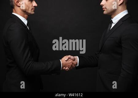 Zwei zuversichtlich stattlichen Unternehmer tragen Anzug, die auf schwarzen Hintergrund isoliert, Hände schütteln - Stockfoto
