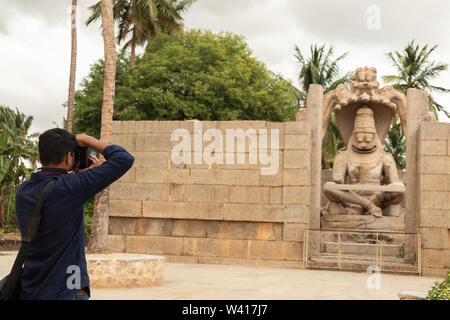 Hampi, Indien Juli 9, 2019: Touristische versuchen zu catpure Ugra Narsimha oder Lakshmi Narsimha an Hampi. Der Mann - lion Avatar von Vishnu - in einem Yog sitzt