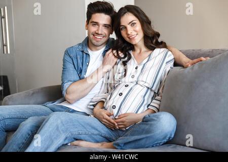 Attraktive junge schwangere Paare entspannt auf einer Couch zu Hause, umarmen - Stockfoto