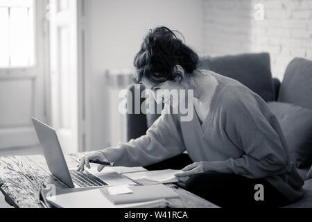 Schwarz-weiß-Porträt von fröhlichen lockeren Frau trägt einen hellen roten Pullover arbeiten und studieren auf dem Laptop auf der Couch zu Hause sitzen. In workin - Stockfoto