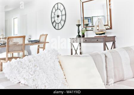 Luxus weißen Sofa in der Nähe von Holz- Tabelle, Spielzeug Schiff auch Kerze auf dem Tisch sehen, Uhr an der Wand befestigt, tagsüber buntes Foto. - Stockfoto