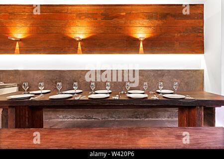 Essbereich im Freien mit orange leuchtet, Weiß Geschirr und Gläser auf dem hölzernen Tisch neben Bänken beleuchtet - Stockfoto