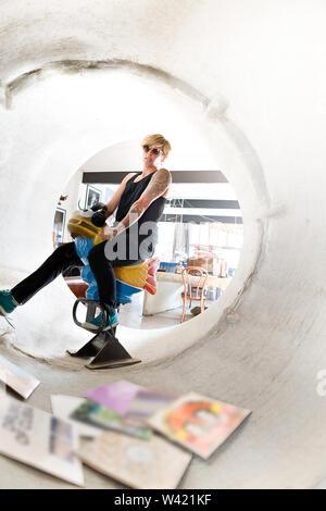 Junge Dame mit Sonnenbrille und ein Tattoo, ein Spielzeug, das Pferd in eine konkrete Leitung einschließlich der Alten Musik vinyl platten - Stockfoto