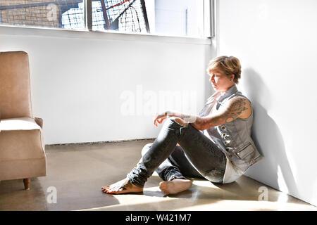 Farbe Gold blonde junge Dame mit Tätowierungen auf dem Körper auf dem Boden sitzend in einem Zimmer, in der Nähe der Fenster - Stockfoto