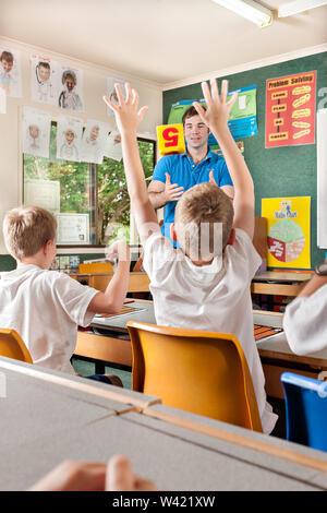 Lehrer lehrt Kinder im Klassenzimmer mit einem Würfel und Fragen, ein Kind die Hände hoch - Stockfoto
