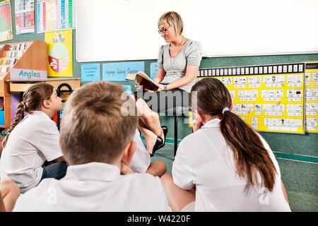 Kinder sitzen auf dem Boden und hören eine Geschichte, die erzählt von der Klasse Lehrer - Stockfoto