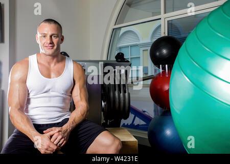 Gesunde Menschen entspannend nach der Arbeit, hat er einen starken Körper, im Zimmer eines luxuriösen Fitnessraum, schwere Übung Werkzeuge in der Nähe von Wall, ein Body Builder sitzen auf einer ben - Stockfoto