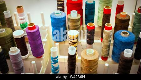Farbe Spulen in der Nähe auf einem Rack mit verschiedenen Größe Gewinde für Nähmaschine gefüllt - Stockfoto