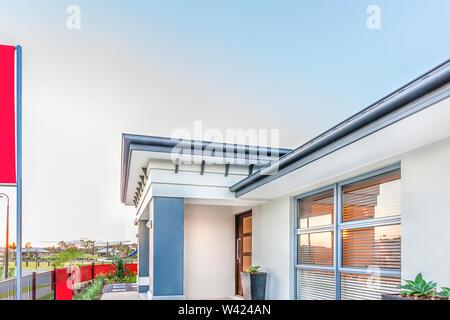 Modernes Haus oder Hotel Vorderseite mit einem Zaun, Es gibt Häuser und grünes Gras Boden aus der Ferne, es ist ein Fenster mit der Reflexion von Sun - Stockfoto