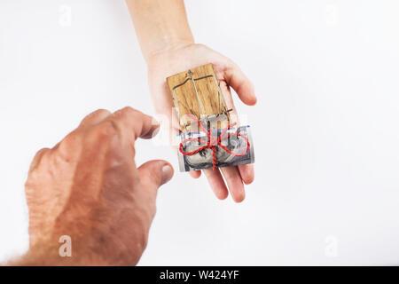 Geld in einer Mausefalle mit einer Hand. Auf einem weißen Hintergrund. - Stockfoto