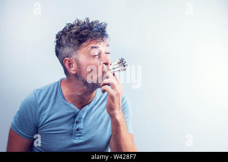 Junger Mann mit vielen Zigaretten in den Mund - Stockfoto