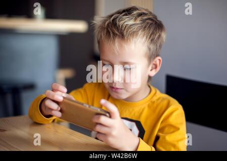Kinder, Technologie und Internet Konzept. Wenig lächelnde Kind Junge spielen oder im Internet surfen auf digitalen Smartphone - Stockfoto