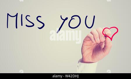 Retro Bild eines Mannes schreiben einer romantisch-Vermisse Dich - Nachricht auf einem virtuellen Bildschirm mit einem roten Herzen, wie er sendet einen Gruß an seine Liebsten oder sweethear - Stockfoto