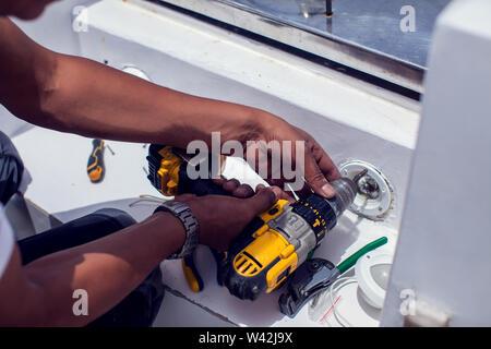 Ein Mann arbeitet mit einem elektrischen Schraubendreher. - Stockfoto
