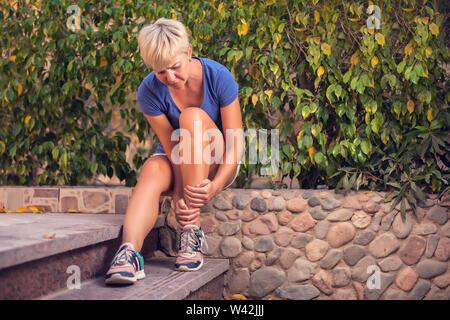 Frau fühlt starke Schmerzen im Fuß. Leute, Sport, Gesundheitswesen und Medizin Konzept - Stockfoto