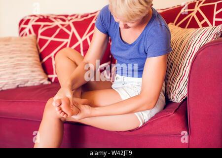 Frau fühlt starke Schmerzen im Fuß zu Hause. Menschen, Gesundheitswesen und Medizin Konzept - Stockfoto