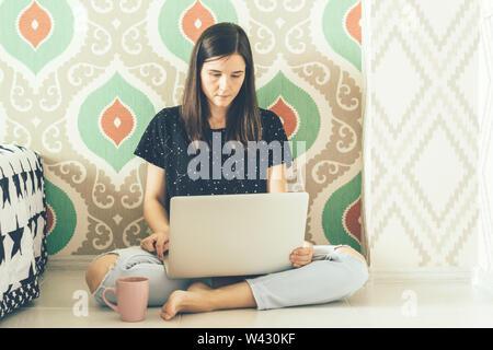 Eine brünette Freiberufler sitzen auf dem Boden ist das Studium Websites in einem Laptop. Modernen Lifestyle. Die Kommunikation der jungen Generation ist das Tausendjährige in - Stockfoto