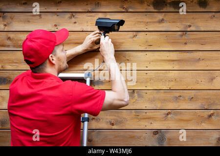 Home security-mann Installation außen Überwachungskamera auf Holz wand Platz kopieren - Stockfoto