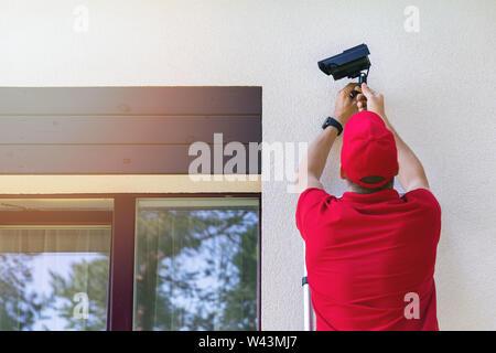 Techniker die Installation im Freien Sicherheit Überwachungskamera auf Haus Außenwand - Stockfoto