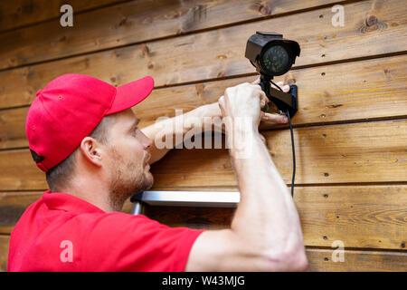 Security System Technician Installation von Überwachungskameras auf hölzernen Haus Wand - Stockfoto
