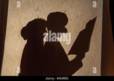Junge Kinder sind hinter einem Vorhang auf der Bühne Silhouette, in Tracht gekleidet, wie ein Junge von einem großen Buch, Drama Bildung liest. - Stockfoto