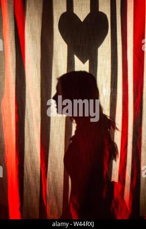 Ein Mädchen gesehen reenacting eine Szene aus einem berühmten Liebe Geschichte auf der Bühne während einer Schule Produktion, auf einen Vorhang. - Stockfoto