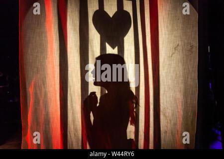 Ein Mädchen auf der Bühne in einer Schule Theater mit Herz über ihrem Kopf gesehen, Casting Silhouetten auf einen Vorhang, als sie die Dirne spielt - Stockfoto