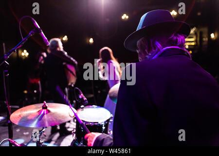 Eine Rückansicht eines älteren Mann spielt Schlagzeug auf der Bühne in einem Nachtclub, unscharfe band Mitgliedern gesehen werden, die im Hintergrund mit copy-Platz auf der linken Seite. - Stockfoto