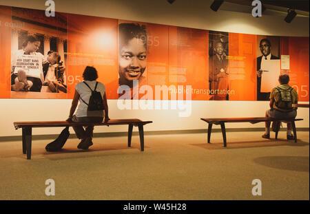 Mehrere Besucher sitzen auf einer Bank das Storytelling der Bürgerrechtsbewegung in der Rosa Parks Library and Museum in Montgomery, AL, USA zu lesen - Stockfoto