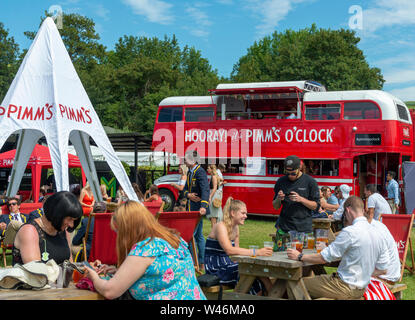 Die Menschen genießen einen Pimms entlang der Themse an der Henley Royal Regatta (2019) Henley-on-Thames, England, Großbritannien - Stockfoto