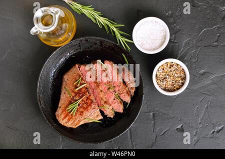 Steak medium Rindfleisch in der Pfanne auf schwarzem Hintergrund, Ansicht von oben, flach Essen legen - Stockfoto