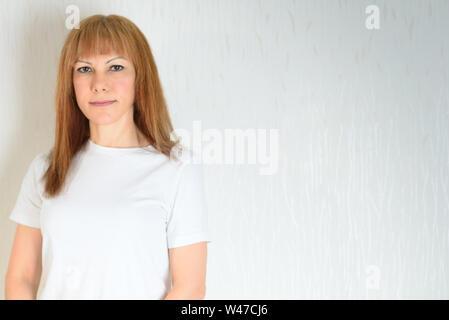 Attraktive Frau mittleren Alters zu Hause entspannen. Eine Frau in der Zeit der Wechseljahre. Blonde, rote Haare reifen älteren Frauen gegen die weiße Wand backgrou - Stockfoto