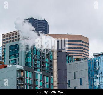 Dampf aus Schornstein vor moderner Gebäude in Seattle. - Stockfoto
