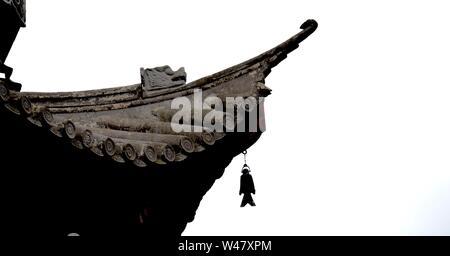 Detail der Kante eines Daches auf eine chinesische Pagode, komplett mit Drachen Schnitzerei und Fisch geformten Glocke. Grau Bekantung von reich verzierten Holzbalken und Fliesen in der silhouet - Stockfoto