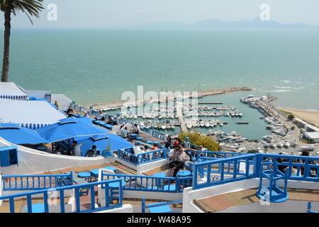 Ein junges Paar Tunsian sitzen in einem Café, Tisch mit Blick auf den azurblauen Mittelmeer und Hafen in der Stadt von Sidi Bou Said, Tunis, Tunesien. - Stockfoto