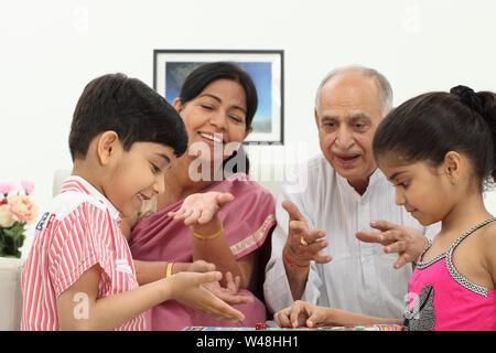 Indischen Jungen und Mädchen spielen Ludo mit ihren Großeltern - Stockfoto