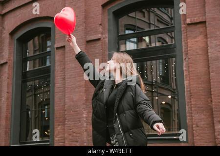 Schöne junge Frau hält ein rotes Herz geformte Kugel, Valentinstag. - Stockfoto