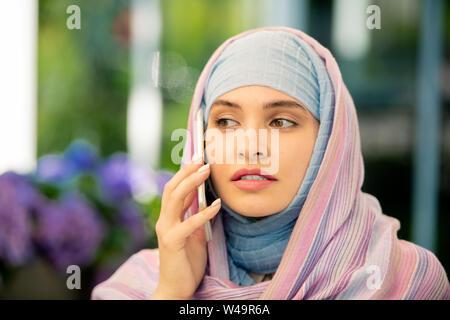 Junge muslimische Geschäftsfrau im hijab sprechen auf dem Smartphone im Freien - Stockfoto