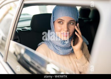Hübsche junge islamische Geschäftsfrau im hijab sprechen auf dem Smartphone im Taxi - Stockfoto