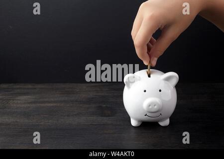 Business oder Finanzen sparen Konzept mit Hand Münze in weißen Sparschwein auf dunklen Holztisch - Stockfoto