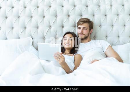 Glückliches junges Paar liegend auf dem Bett in einem Schlafzimmer und mit digital-Tablette. - Stockfoto