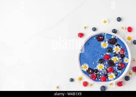 Smoothie Schüssel oder schöne Creme aus blauen Spirulina, gefrorene Beeren, Banane und Kokosnuss mit kamillenblüten auf weißem Marmortisch. gesundes Frühstück - Stockfoto