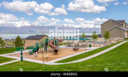 Panorama rahmen Spielplatz und Häuser auf ein Wohngebiet mit Blick auf den See und die schneebedeckten Berge. Weiß blühende Bäume säumen den Weg bei bewölktem bl - Stockfoto